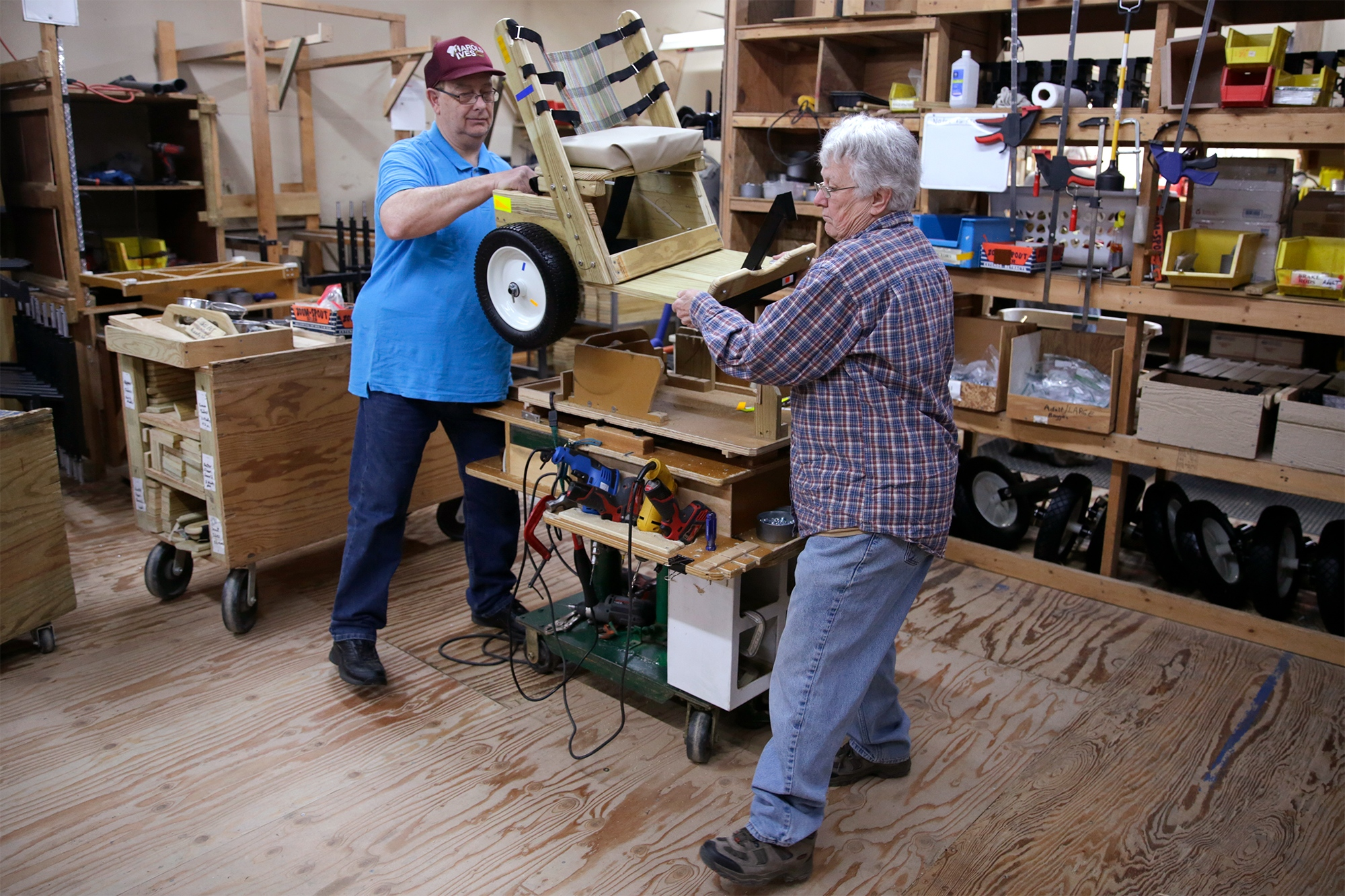 James Kingsley and Nancy Gentzsch move a completed children's mobility cart off their workbench on Tuesday April 9, 2019 in Columbia. The pair are volunteers at Mobility Worldwide, where the carts are built. Volunteers work in teams to construct the devices quickly.
