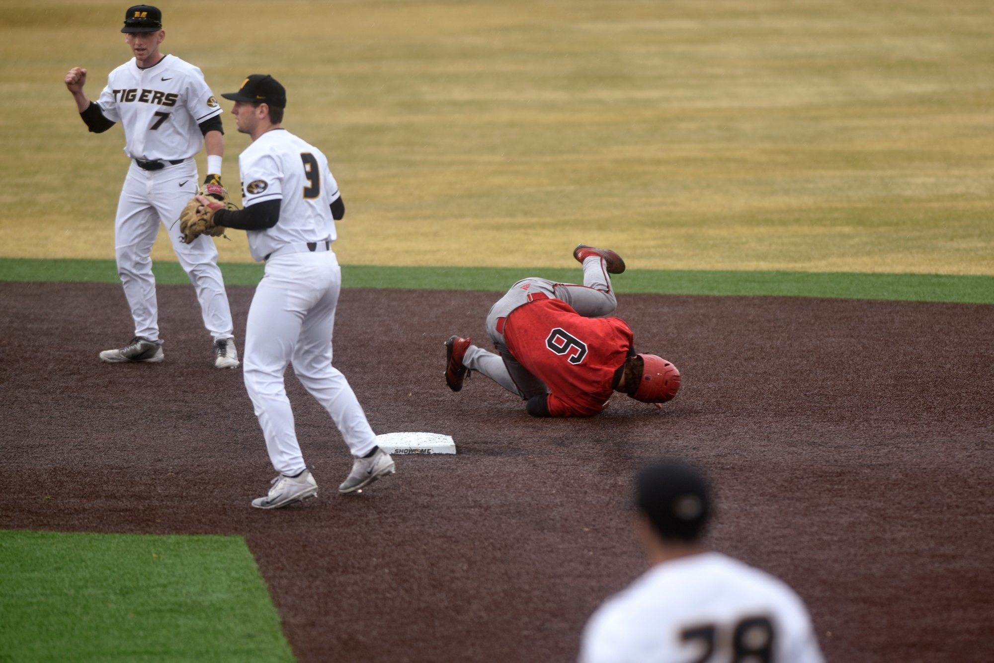 As Missouri midfielders Chris Cornelius, left, and Mark Vierling, center, watch for a throw from the Missouri catcher, Arkansas State's Will Zimmerman summersaults past second base during a game on Wednesday, March 13, 2019 at Taylor Stadium. The Tigers' next game will be on Friday against the Arkansas Razorbacks in Fayetteville.