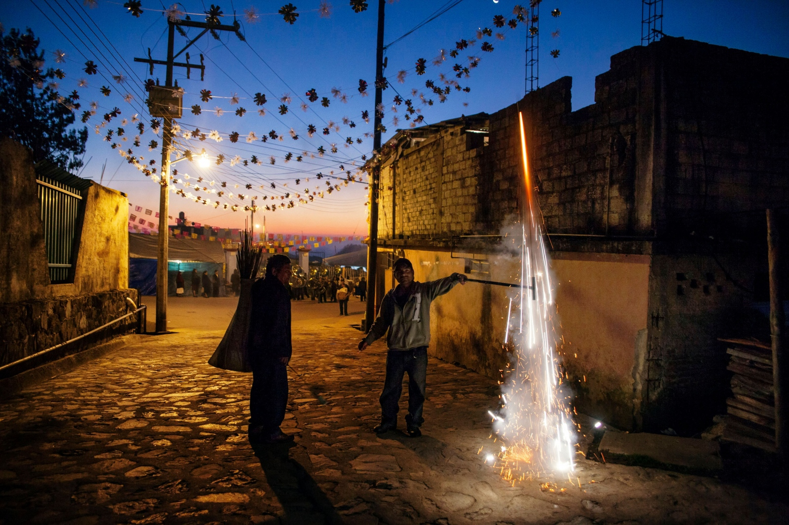 TOTONTEPEC VILLA DE MORELOS, JANUARY 20, 2012. Men set off fireworks before sunrise in the village of Totontepec Mixe as a celebration of the saint's birthday. The men headed a procession of villagers who would carry the saint's image around the village in a ritual parade.