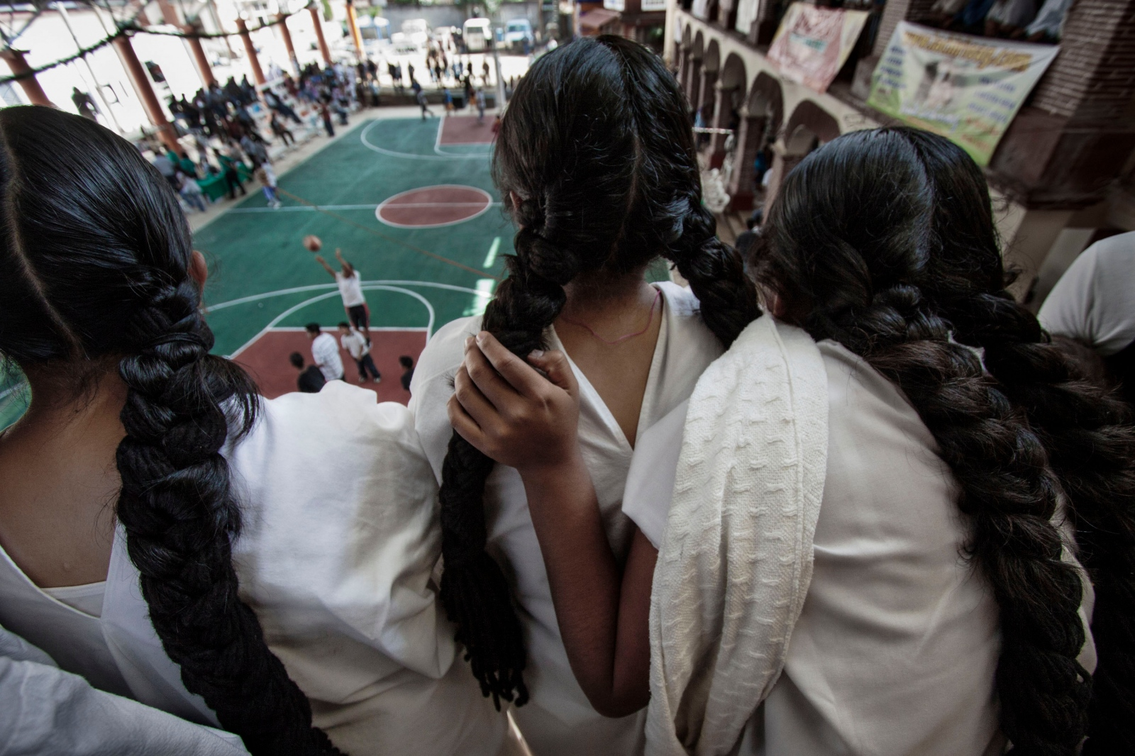 SAN CRISTÓBAL LACHIRIOAG, NOVEMBER 21, 2009. Indigenous Zapotec girls in traditional dress watch a basketball game in San Cristobal Lachiroag.