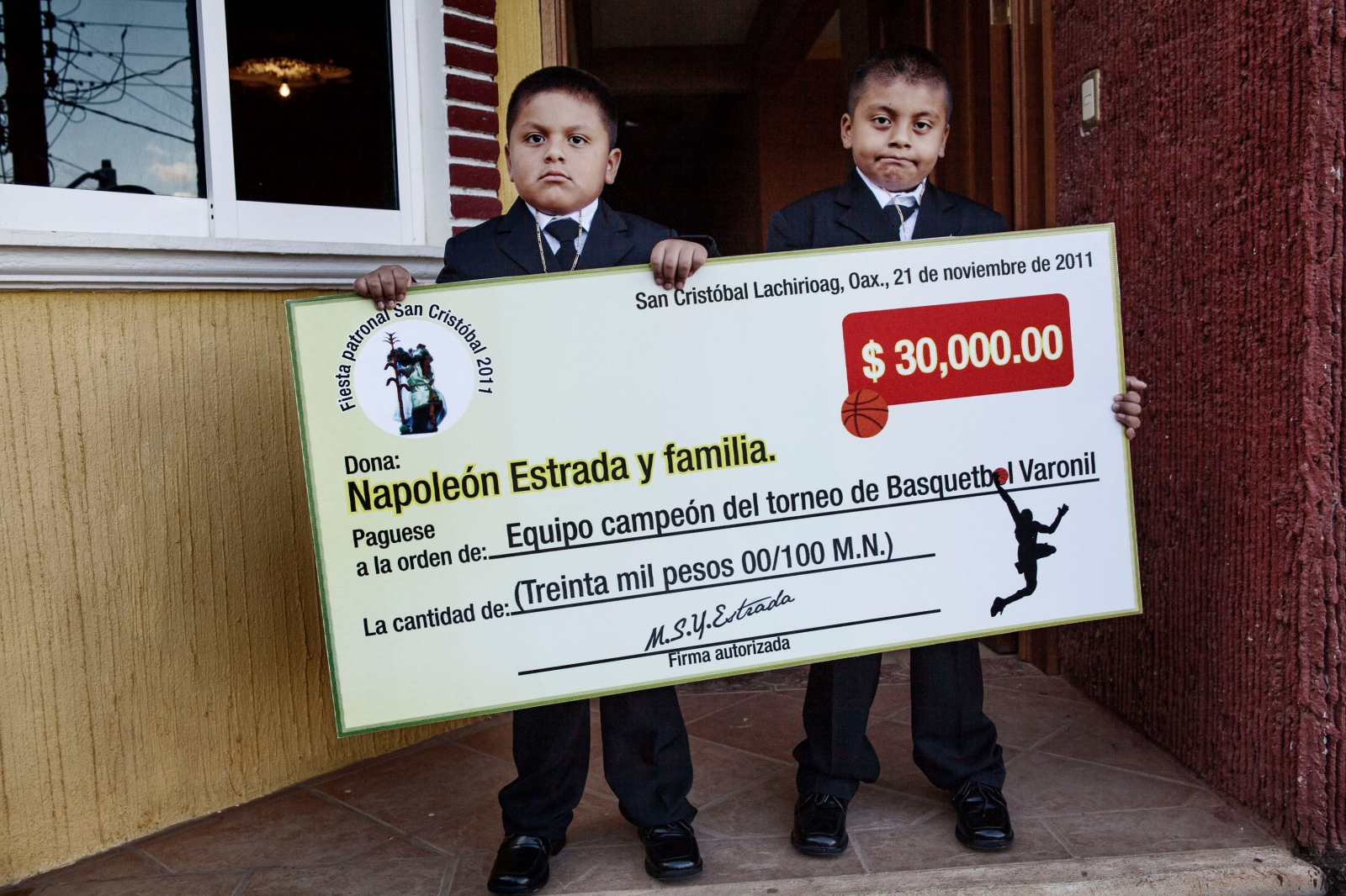 SAN CRISTÓBAL LACHIRIOAG, NOVEMBER 19, 2011. Left, Saul Estrada Pablo, age 4; right, Martin Estrada Pablo, age 6. Both boys are sons of Napoleon Estrada, a migrant living in Escondido, California. The boys are American citizens, but their father is in the U.S. illegally. Afraid of not being able to recross the border if he returned to Mexico, Napoleon Estrada sent his sons- who had never been to Mexico- to award the $30,000 peso prize he was donating for first plaze in the basquetbol tournament. Photo taken in San Cristobal Lachirioag on November 21st, 2011.