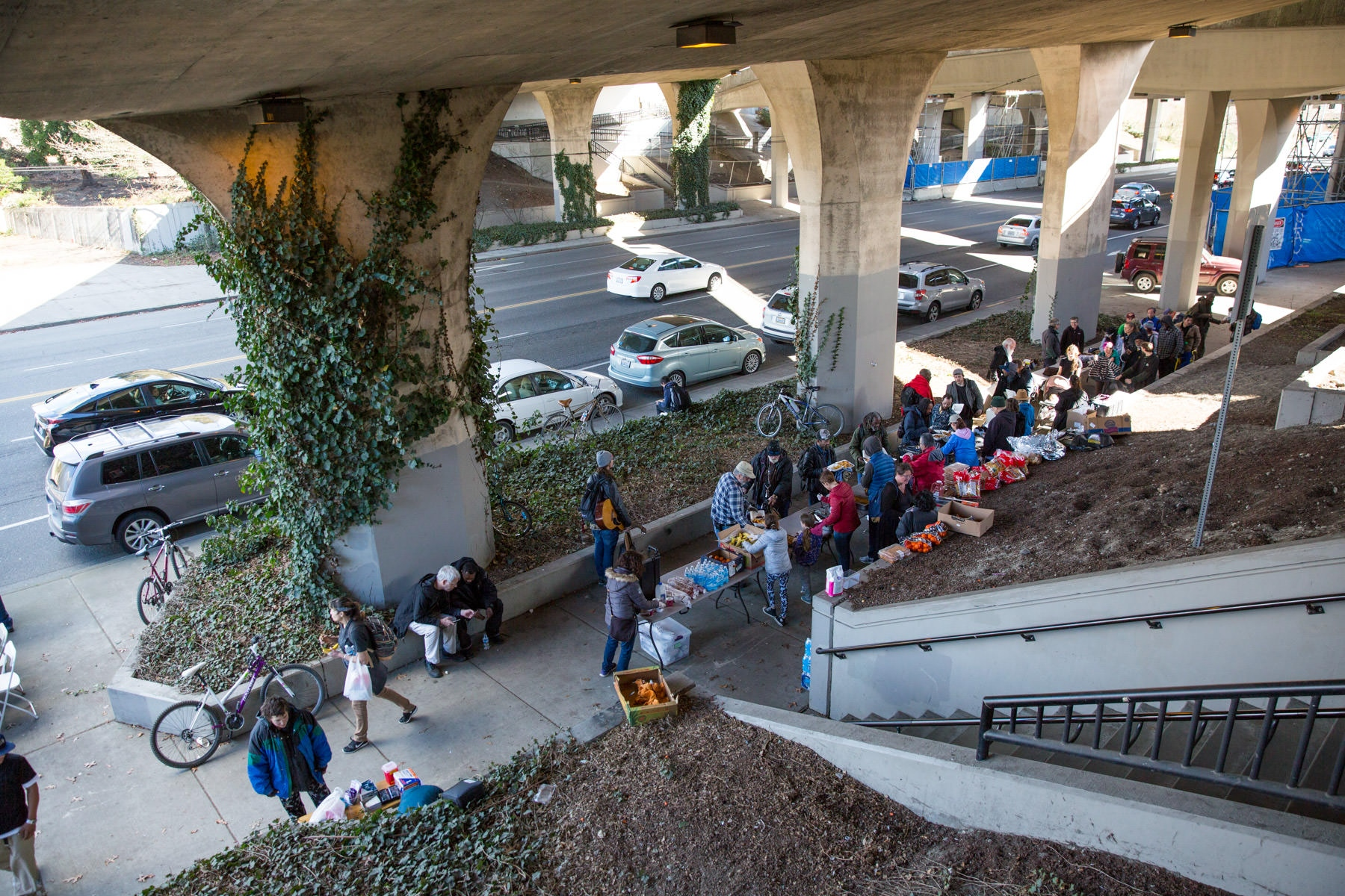 Volunteers from the Rainier Popup Kitchen bring dishes to serve on a sidewalk beside a busy road under an Interstate 90 bridge, where around 100 diners eat at folding tables and chairs. Ms. Vestal and Mr. Kitcheon are regulars.   For the New York Times