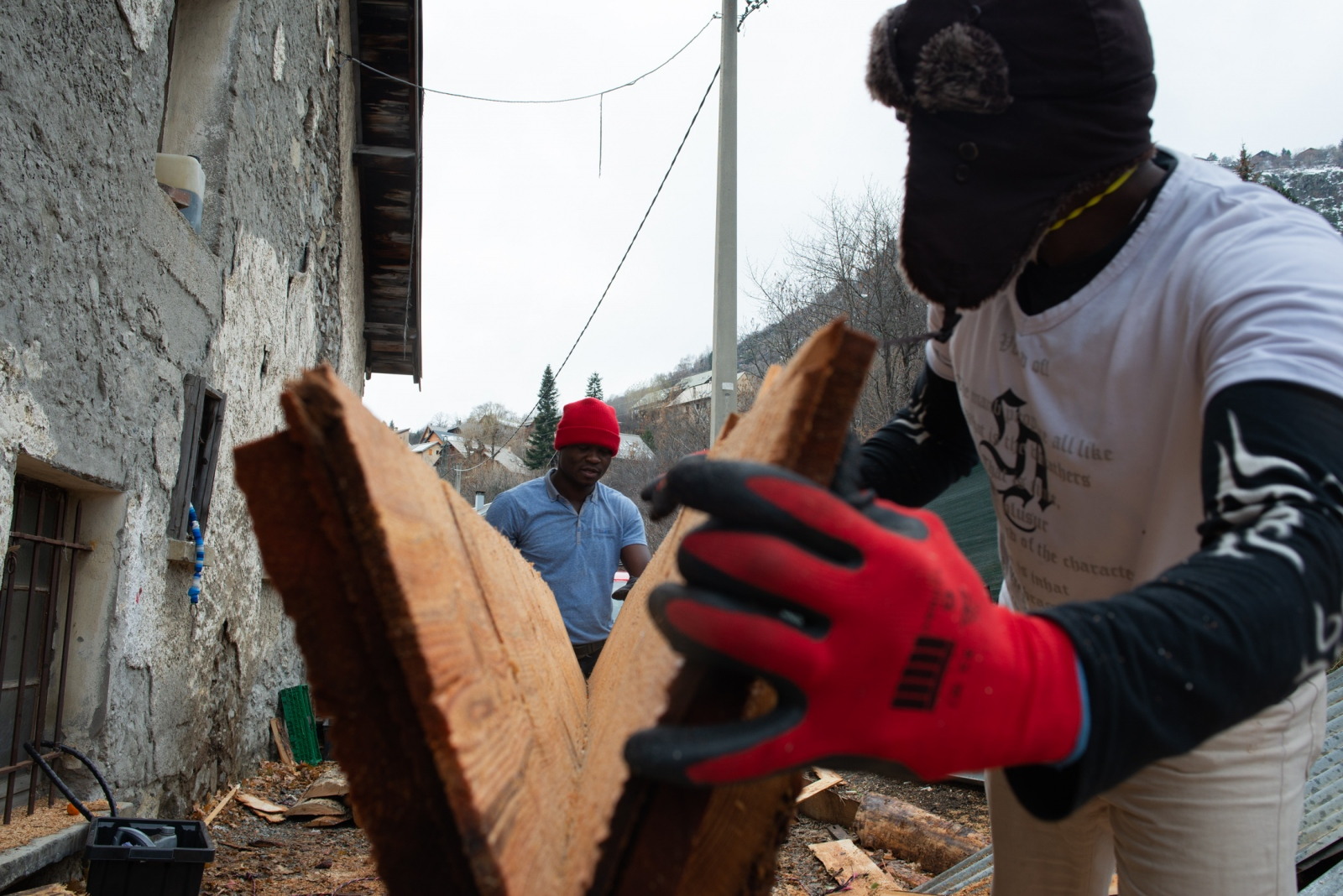 Nigel* and Jacques* are cutting wood for the communal house, Chez Marcel. 15m squared of wood was bought by an ngo and donated to the house where asylum-seekers live. Briançon, France. December 2018.