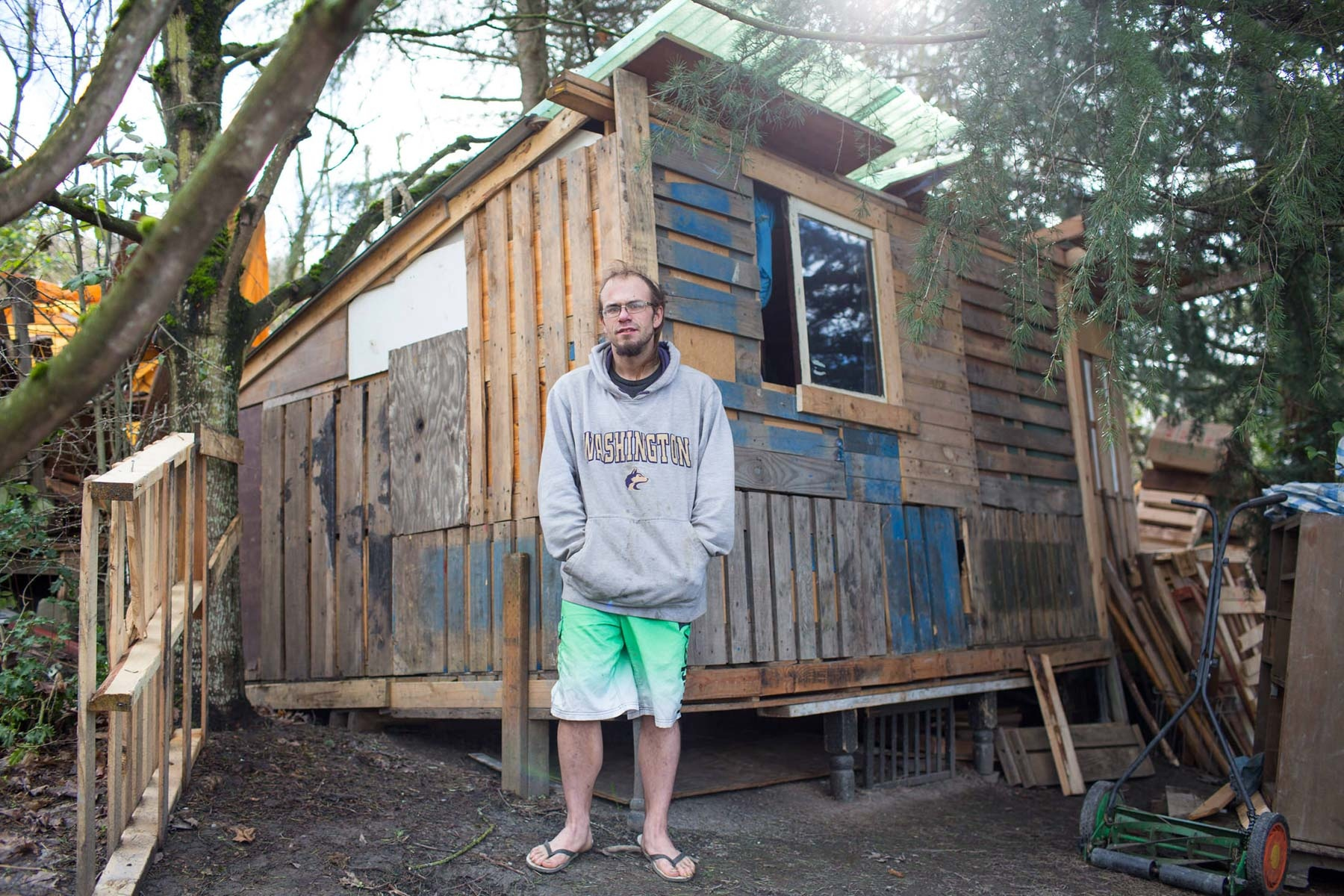 Chris Erickson, 32, in front of the tiny home he built at the homeless encampment known as 'The Jungle' next to the onramp of I-90 in Seattle. 'This is the house that we built'  for the Guardian