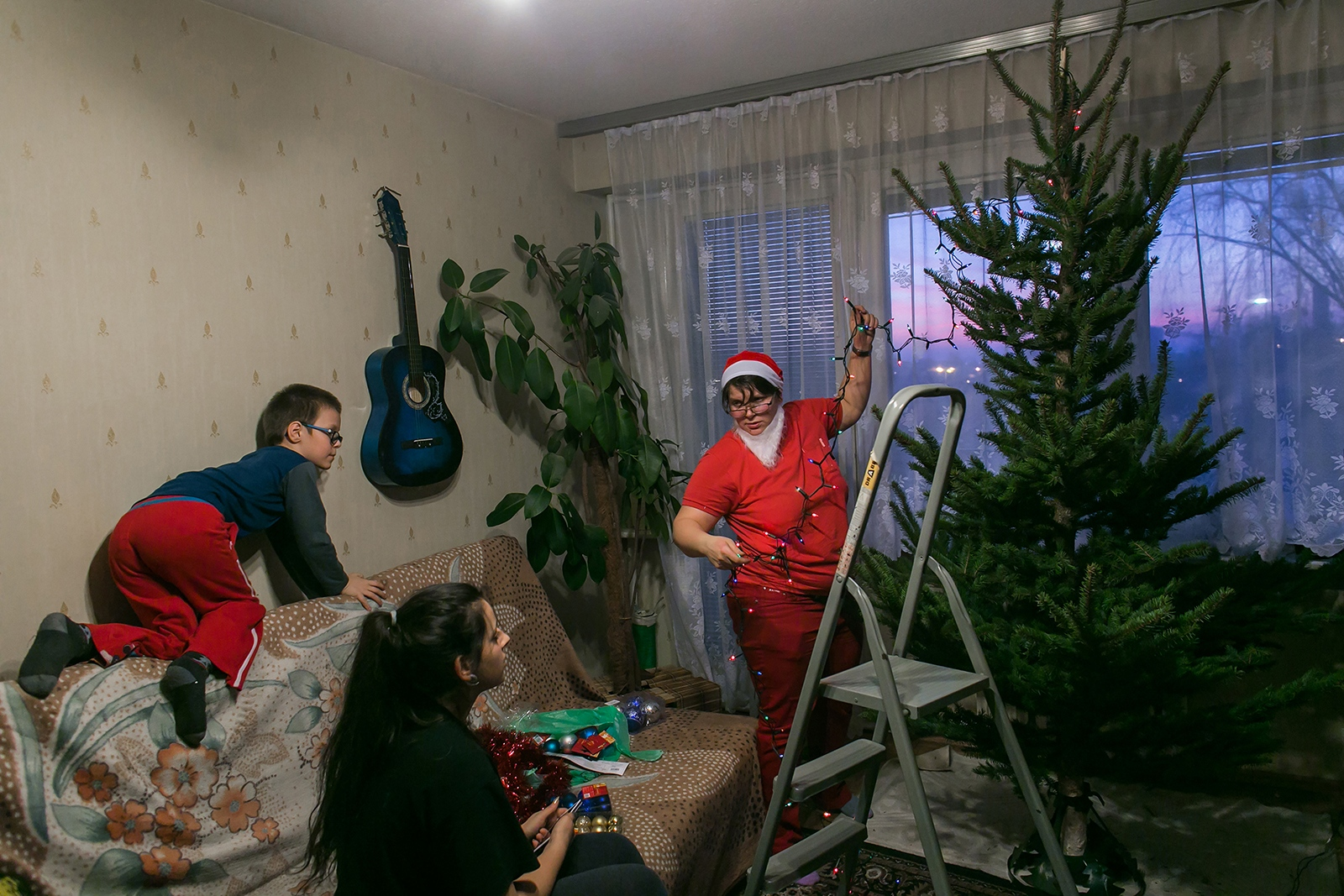 Getting ready for the first Christmas Eve in their own apartment. Antek moved out from his grandparents' home and is living permanently with the girls for the first time. (Featured: Antek, Natalia and Honorata )  Kalisz, Poland 2015
