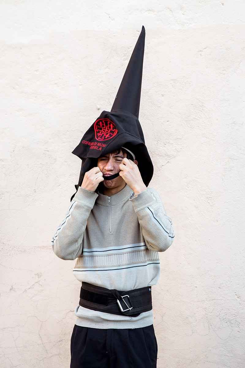 Brother Marco Castañeda tries on the conical hat known as capirote.