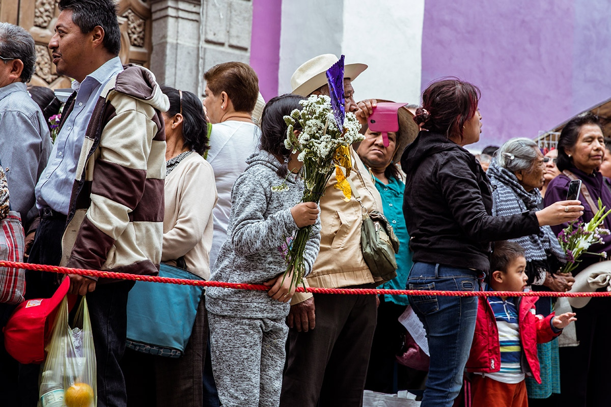 "A girl holds a bouquet of flowers outside the Temple of St. Monica during Holy Week. The temple holds one of the most venerated sculptures in the city: ""El Señor de las Maravillas."""