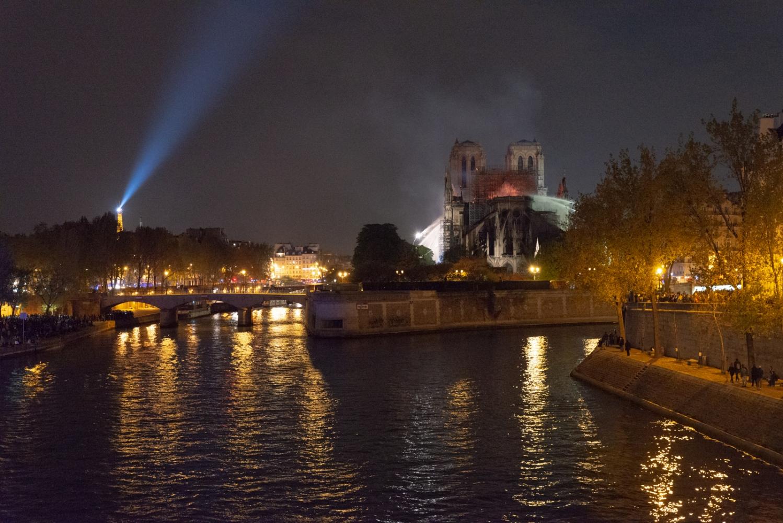 Incendie de Notre Dame de Paris - Avril 2019 - La cathédrale en flamme sous le projecteur de la tour Eiffel.