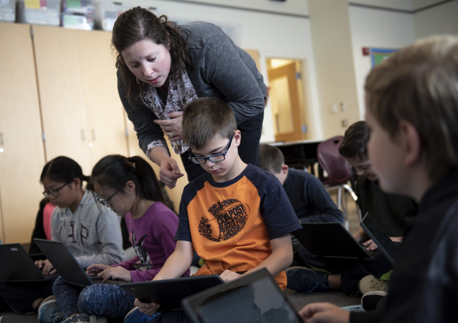 Tara Pollick helps her student, Caleb Kraft, think about a question showing in the laptop in the STEM class on Oct. 17, 2018, at Ferguson Township Elementary School in State College, Pa. Pollick, a STEM teacher at Ferguson Township Elementary School, said she liked helping her students approach solutions.