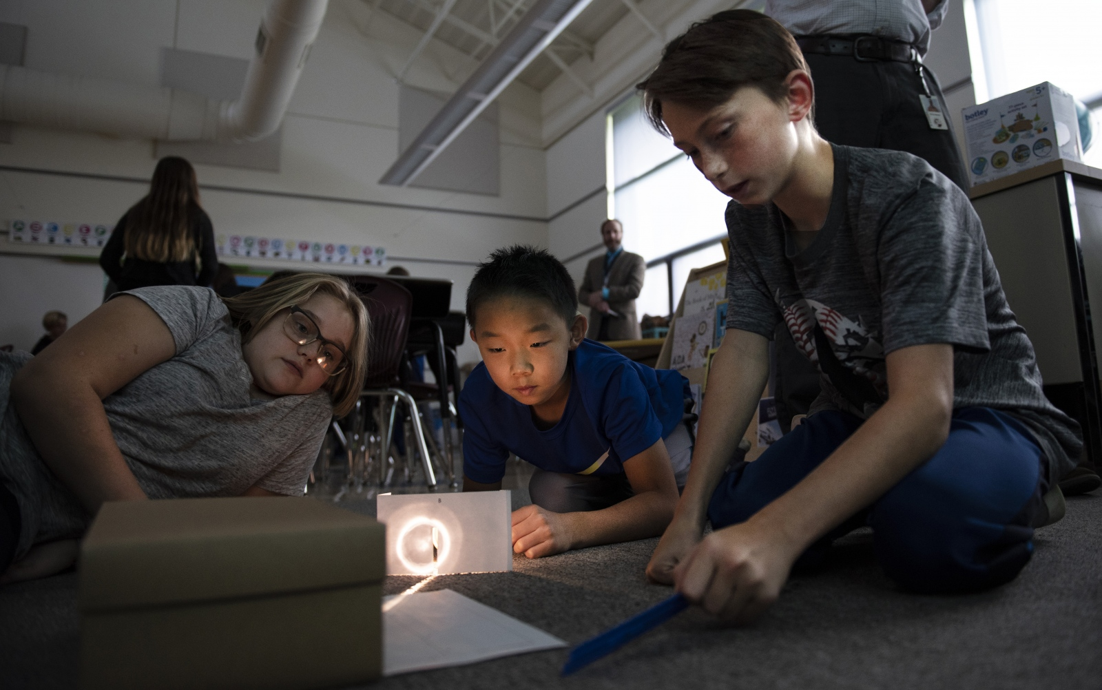 Phoebe Jensen, left, William Liu, middle, and Tiaden Markle, look at the light of a class experiment in the STEM class on Oct. 17, 2018, at Ferguson Township Elementary School in State College, Pa.