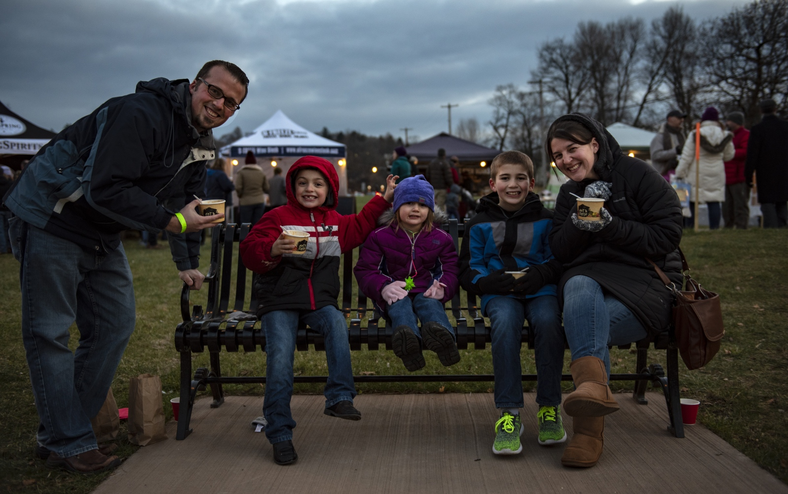 Caton's family sit together eating the food from Bellefonte Lights Winter Market Saturday, Dec. 8, 2018, in Bellefonte, Pa.