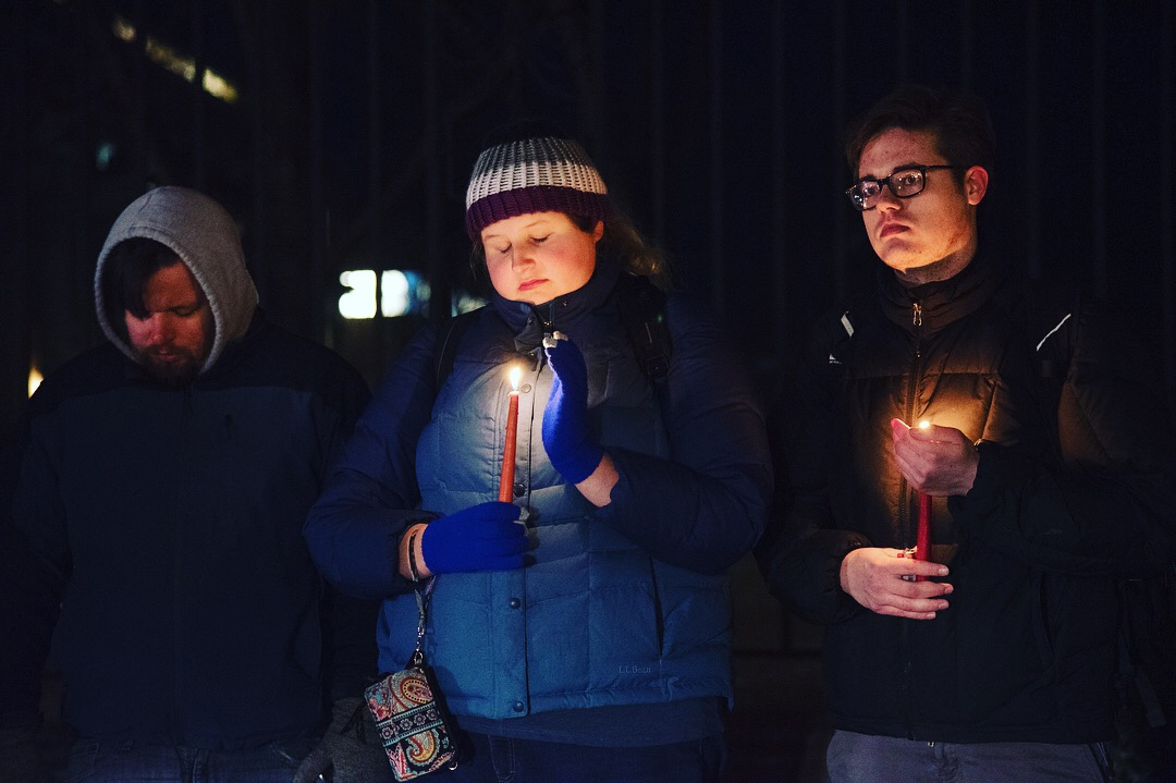 A group of people stands at Allen gate holding candles to pray in Dec 2017, in State College, PA.