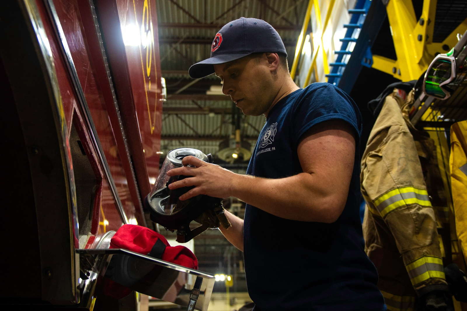 Christophe Cheroret checks a smoke helmet at Alpha Volunteer Fire Department, Monday, April 9, 2018, in State College, Pa. He had a training session each Monday as a volunteer firefighter.