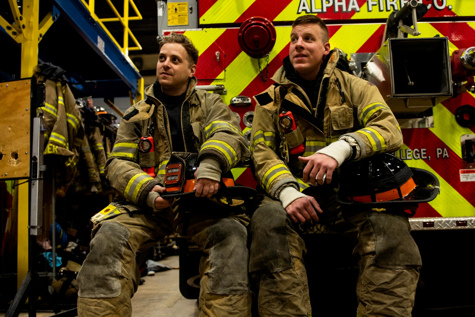 Christophe Cheroret and his friend James Watkins look at their colleagues talking about their training plans at Alpha Volunteer Fire Department, Monday, April 9, 2018, in State College, Pa.
