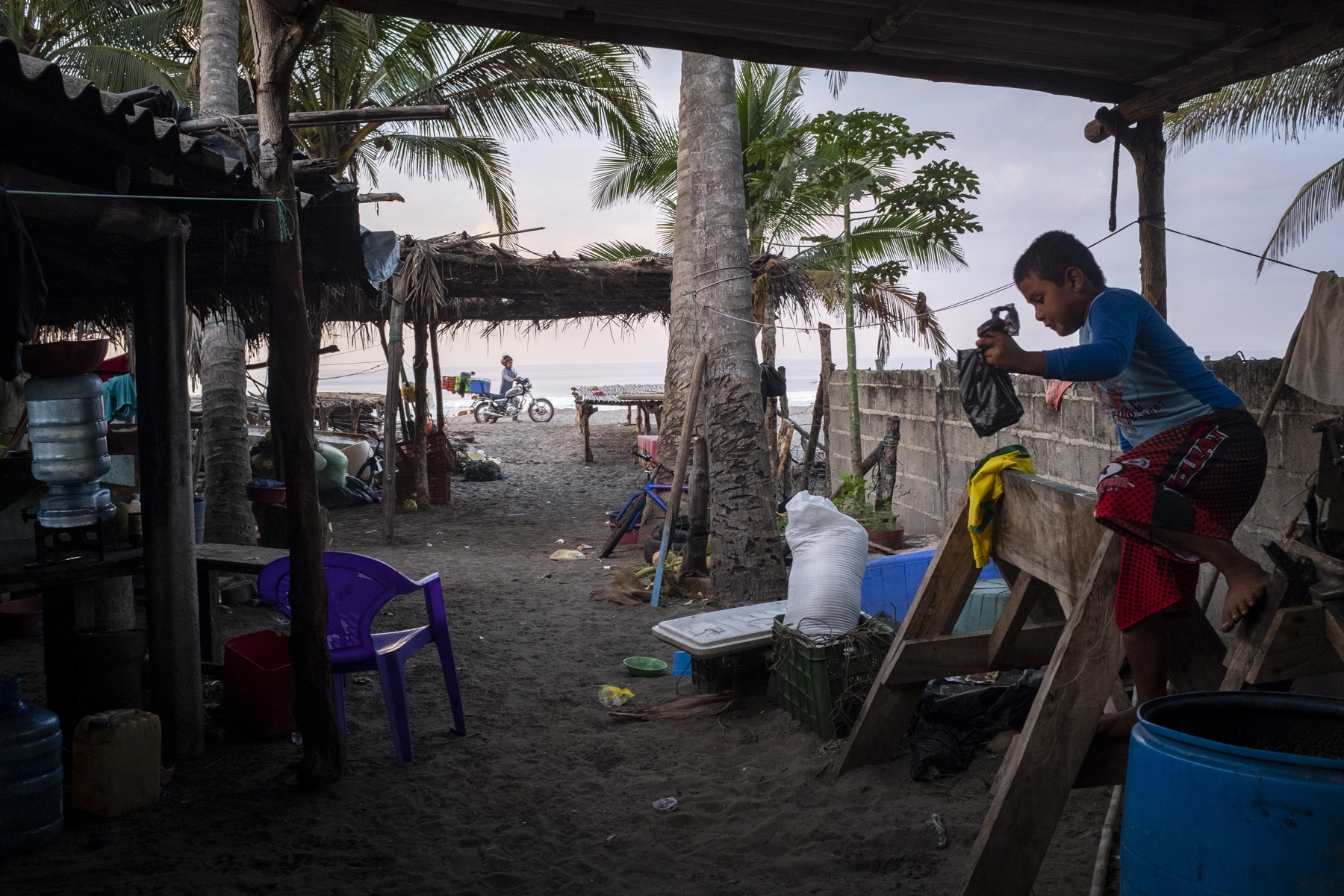 At dawn, Josue Elias, 8, buys bread from a local merchant to feed his father and older brother when they return from fishing. Most fishermen in the community work during the night as it increases their chances of catching fish and making a bigger profit.