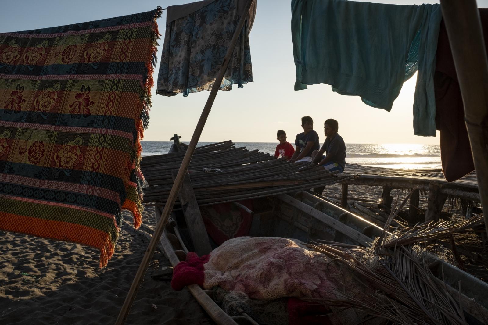 Melvin Elias (middle), 16, waits for a friend before going fishing near his home in La Barra de Santiago, El Salvador.