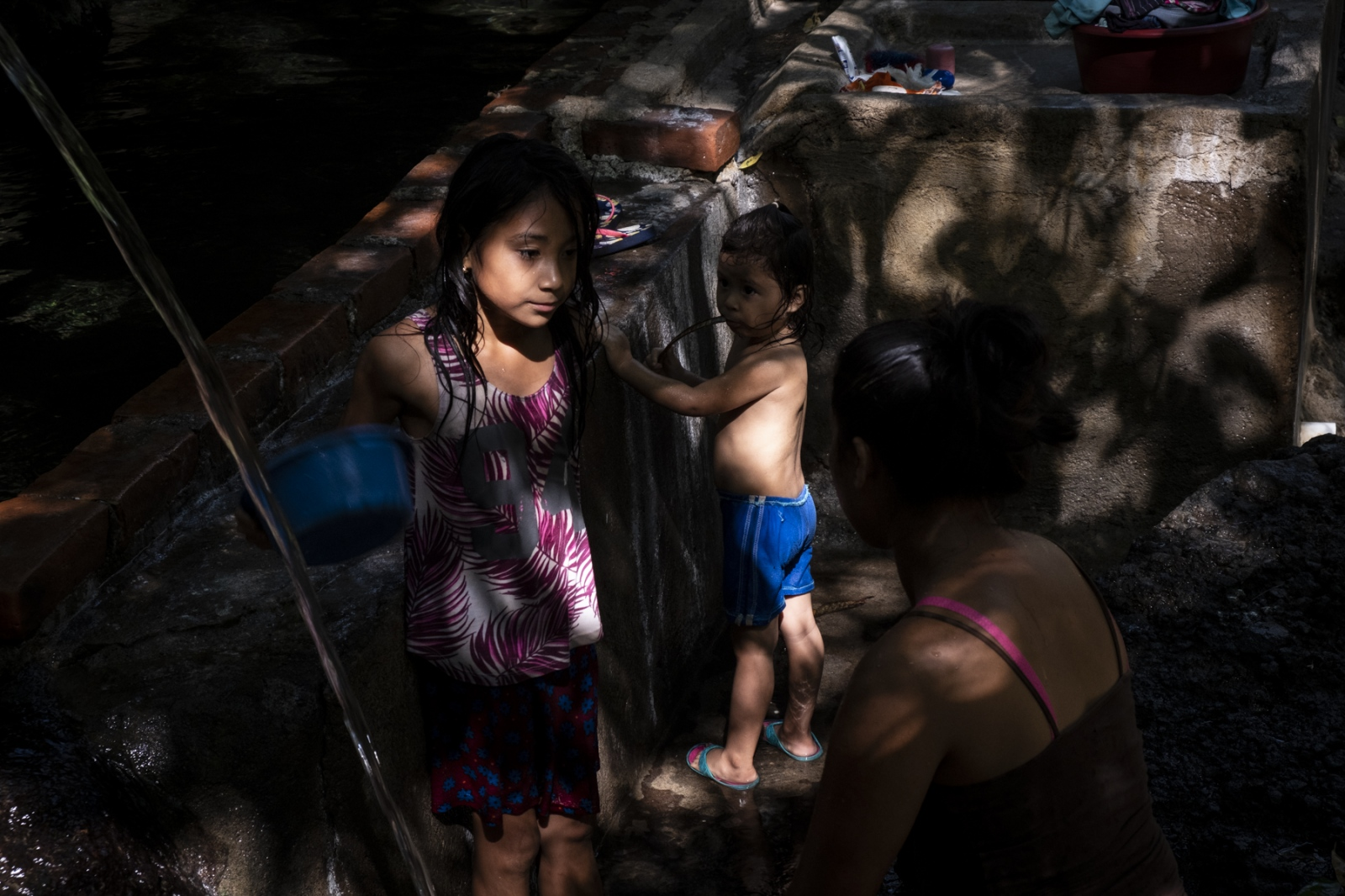 A family collects water from a makeshift plumbing system in Tres Calles, Usulután. Being the only spring in the community, many families walk up to 2 hours in the dry season to collect water for their homes.   According to the WFP, the surge in number of unaccompanied minors who arrived to the United States from El Salvador between 2015 and 2016 is linked to the period of hightened food insecurity in the country's Dry Corridor.