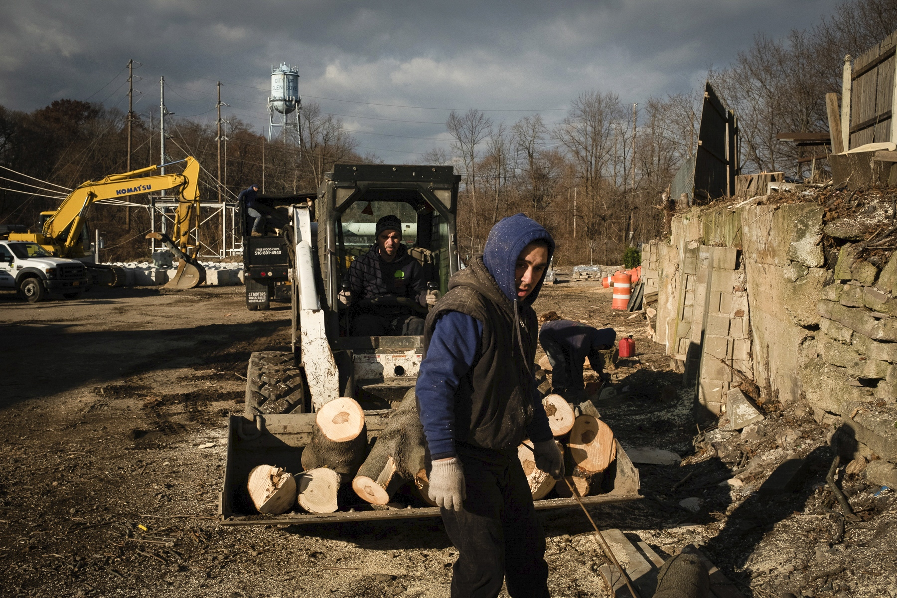 "Erik Villalobos and his father, Guillermo Villalobos, remove trees from a parking lot in Long Island, New York. Since graduating from college last summer, Erik has been helping his dad with the landscaping business he inherited from his own father. ""When I left home, I never thought I would be cutting down trees,"" Guillermo Villalobos said. ""I came to do what I learned as a child."""