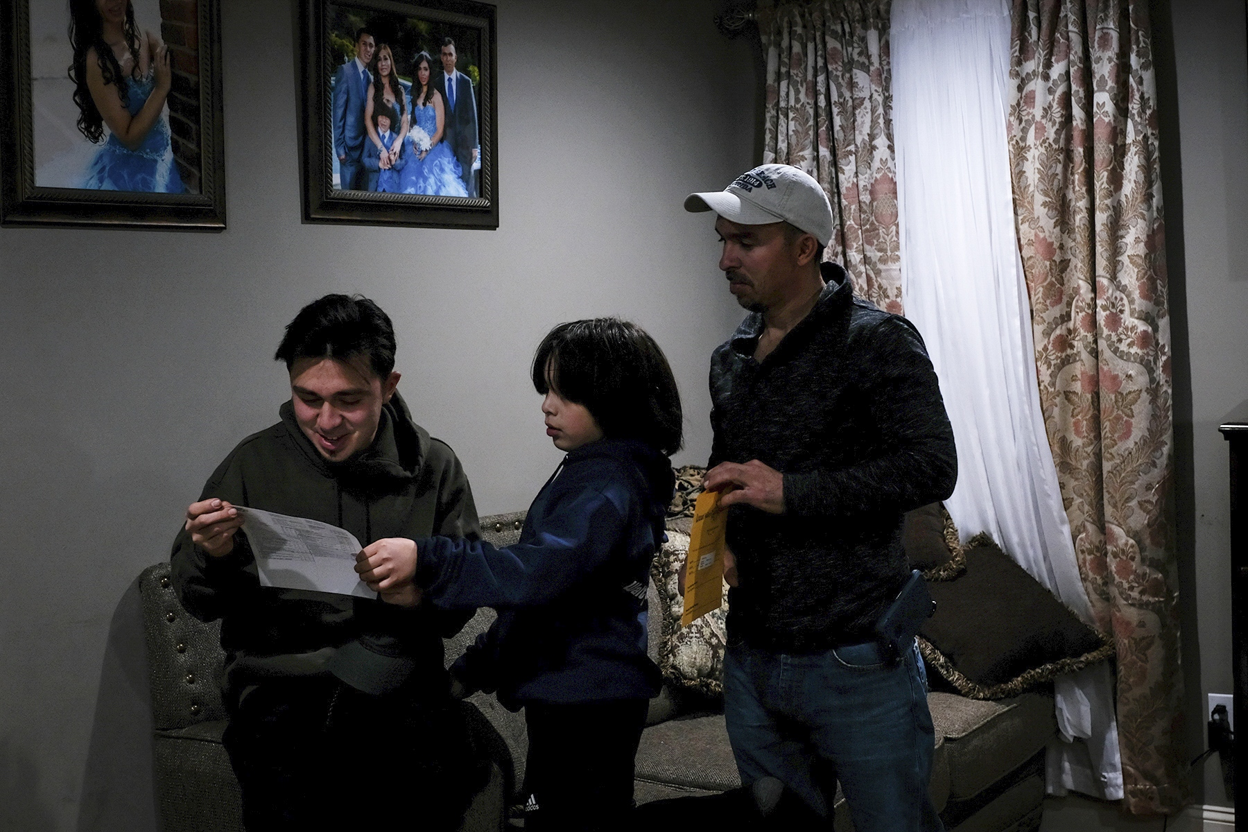 Erik Villalobos reviews his younger brother's grades after he arrived home from school.