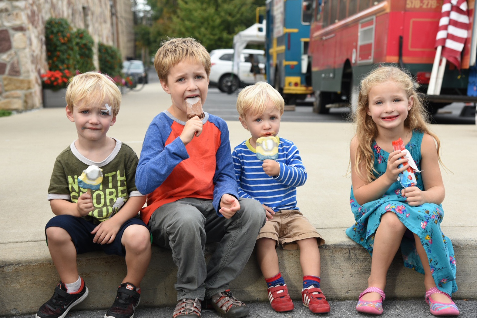 Four children sit together eating ice creams at a local food truck festival in State College, PA, on Sep 15, 2017.