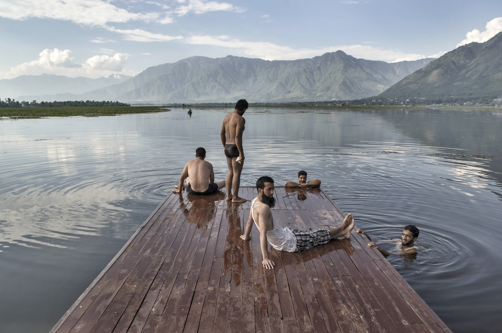 """Photography image - A group of boys swim in the Dal Lake of Srinagar, the only safe and free area during the curfew very often imposed by the Indian authorities. The valley of Kashmir today is one of the most militarized zones in the world but a Persian poet, amazed by its beauty, in the XII century wrote: """"If there is a paradise on earth, it is here""""."""