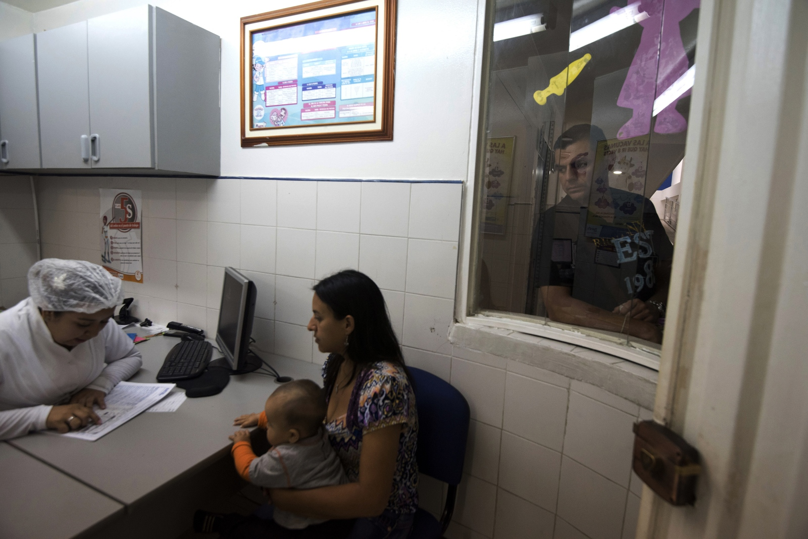 A Venezuelan mother and her child receive instructions by the nurse of Villa del Rosario hospital about a vaccine for the child the father waits, hospitals in Cucuta can't attend the hundred of Venezuelans arriving  on  March, 2017 in Cucuta, Colombia