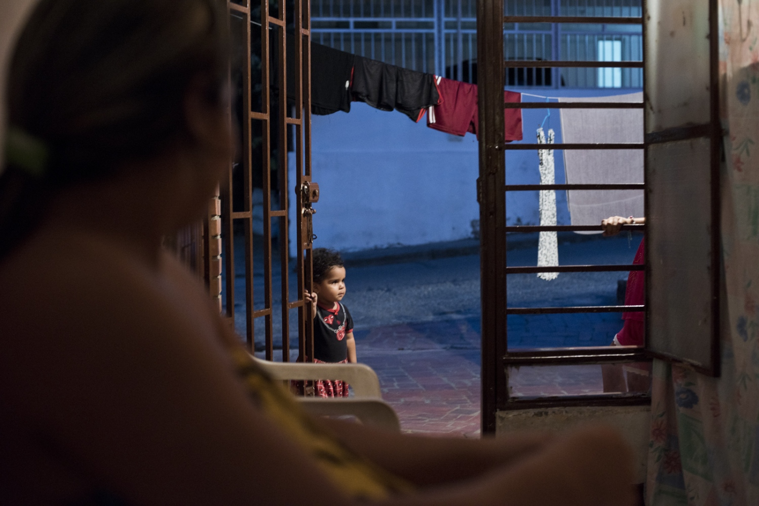 Gerlimar Pastran looks at her daughter outside of the small room where the family lives in La Libertad neighborhood on March  2017 in Cucuta, Colombia.
