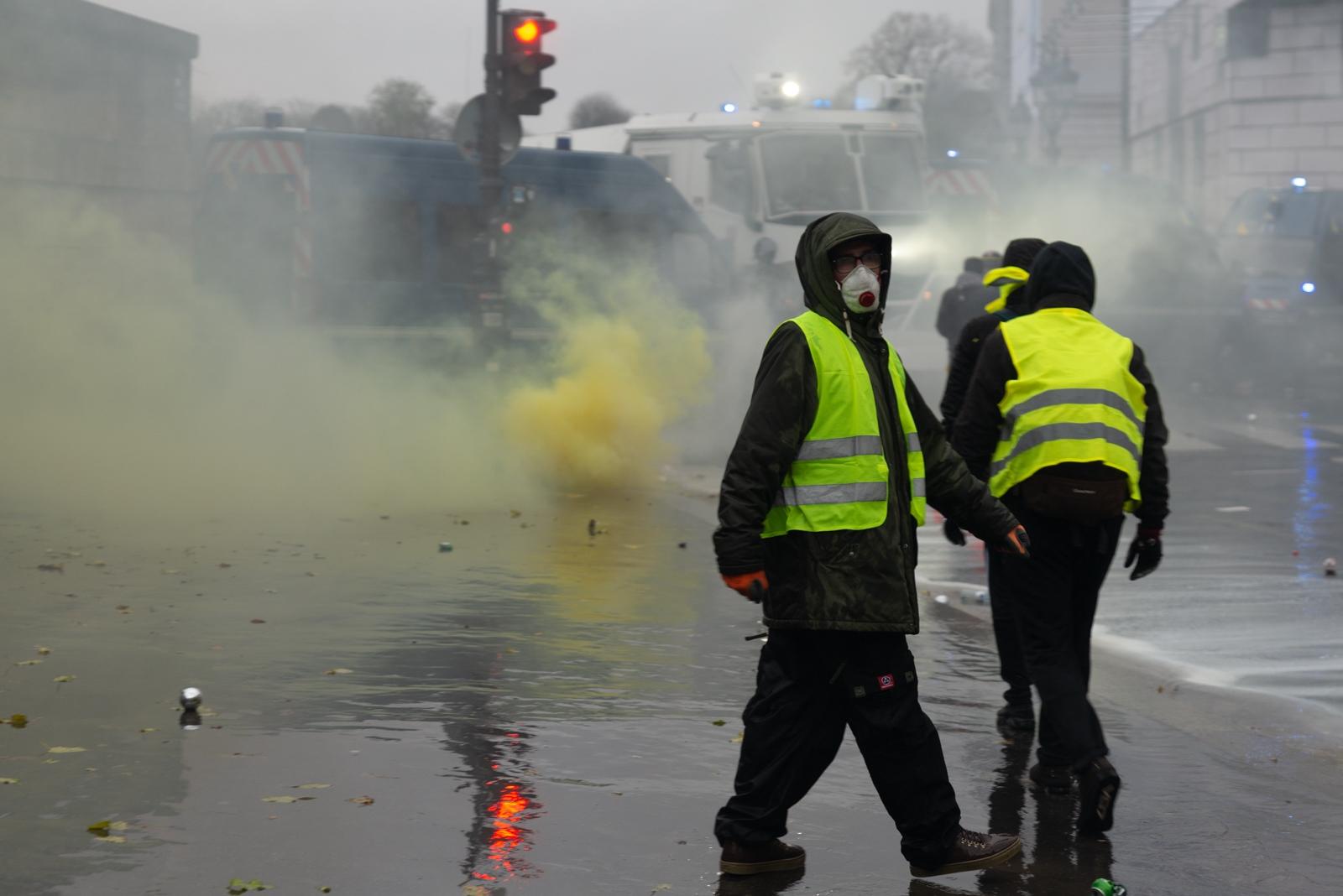 Un Gilet Jaune avec un masque à gaz dans la rue de Rivoli sous les fumées de gaz lacrymogènes et de fumigènes, lors d'une manifestation à Paris le 1er décembre 2018. Paris - Acte III - Rue de Rivoli le 1er décembre 2018.