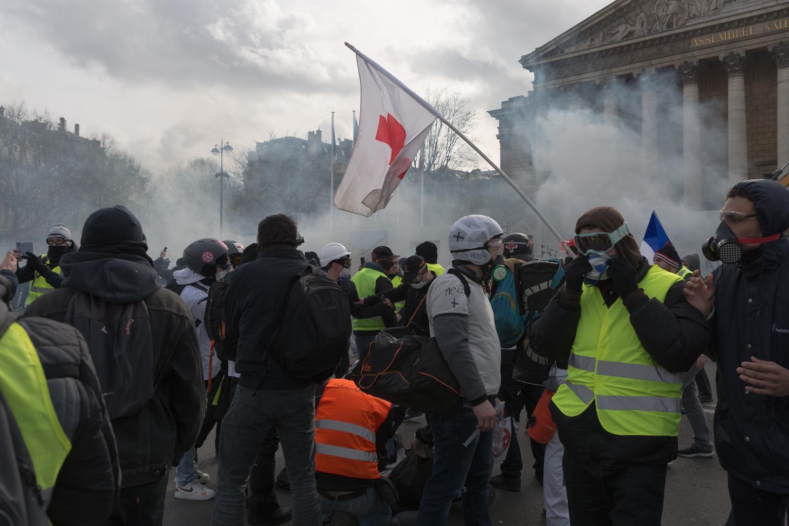 """Des """"Streets Medics"""" soignent un manifestant blessé par une grenade de désencerclement. Le journaliste David Dufresne dénombrait au 9 février 2019, 183 manifestants sérieusement blessés à la tête, 19 éborgnés et 4 ayant eu une main arrachée en raison de l'emploi par les forces de l'ordre de LBD, de grenades de désencerclement et de grenades lacrymogènes. Paris - Acte XIII - Devant l'assemblée nationale le 9 février 2019"""