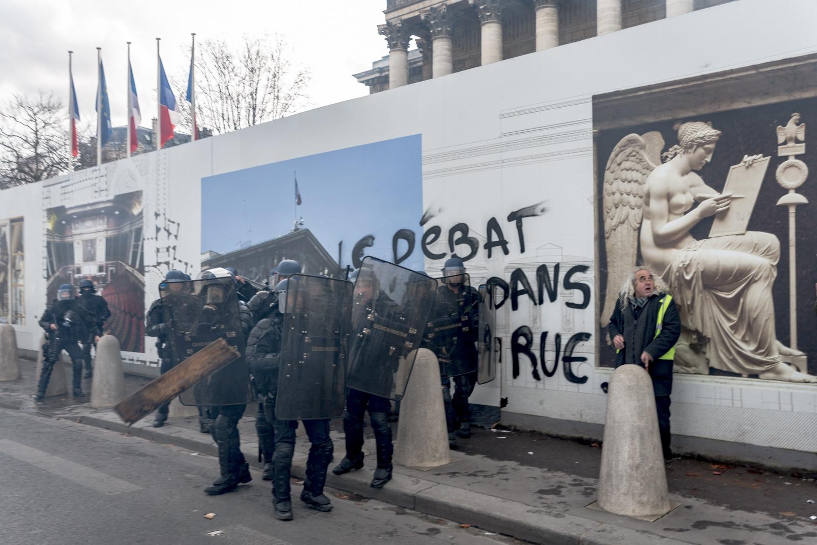 Jet d'une planche en bois sur des membres de la gendarmerie à côté d'un gilet jaune apeuré. Paris - Acte XIII - Devant l'Assemblée Nationale le 9 février 2019