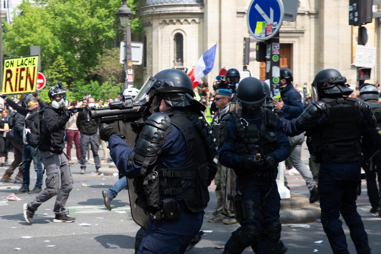 """1er mai 2019 - Paris - Manifestation Une pancarte """"On lâche rien"""" derrière un policier tenant un LBD."""