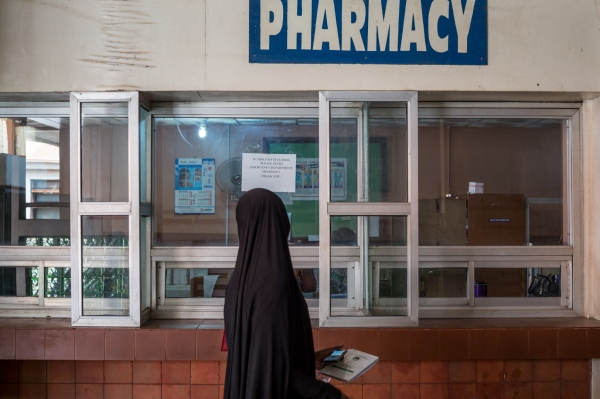 A woman stands in front of a counter in the pharmacy at UCH, Ibadan as she waits to be collect the drugs she purchased.