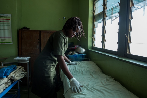 Zainab preps a bed to be used by a nurse. Zainab works as a health assistant in the University College, Hospital, Ibadan.