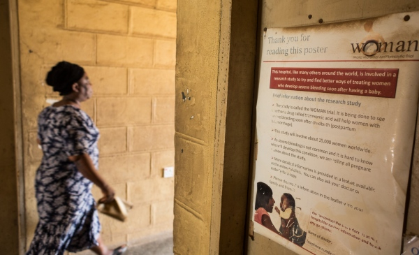 A woman walks past a poster of the WOMAN Trial which was conducted in over 50 hospitals in Nigeria. By the end of the trial which began in 2010 and ended in 2017, the results from the trial proved that  Tranexamic acid was effective for postpartum hemorrhage thus reducing the number of maternal mortality in Nigeria