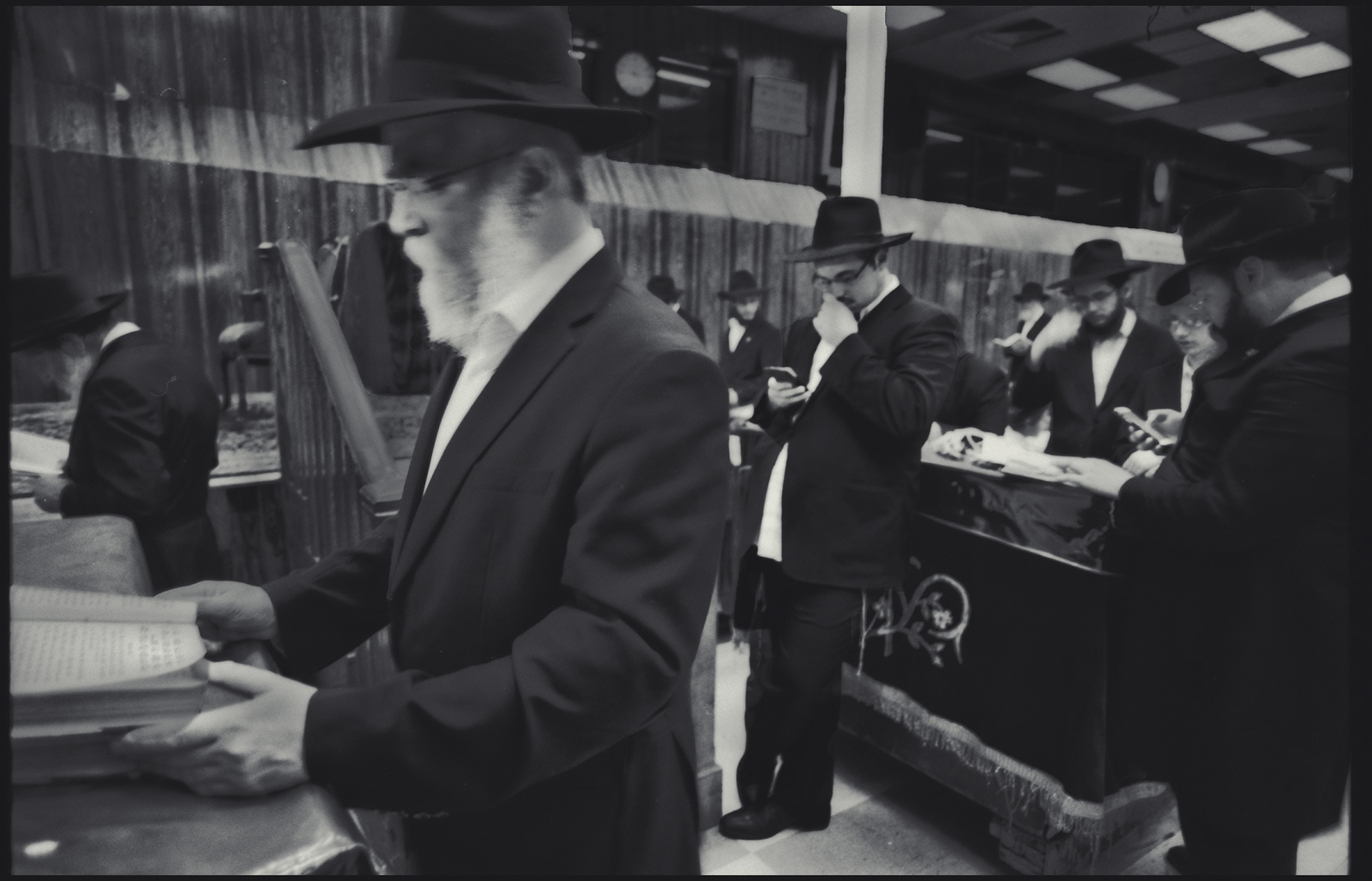 As Rabbi turns the Torah, two men work their mobile phones during Friday prayers. Chabad  Lubavitch, Prospect Heights, Brooklyn, NY. 2017.