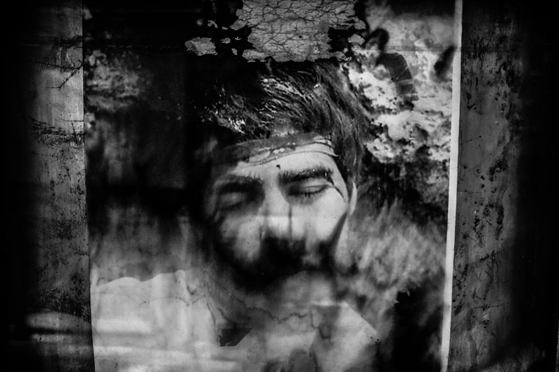 """Faded portrait of Iranian martyr Amir Haj Amini, who was martyred in March of 1987, as a result of a mortar shell injury. This image became popular among the Iranian people after the war as the most beautiful martyr image. Because of that, many people use this image for the graves of unknown martyrs, without name or identity. Tehran, from my long-term project """"Martyr is Alive""""."""