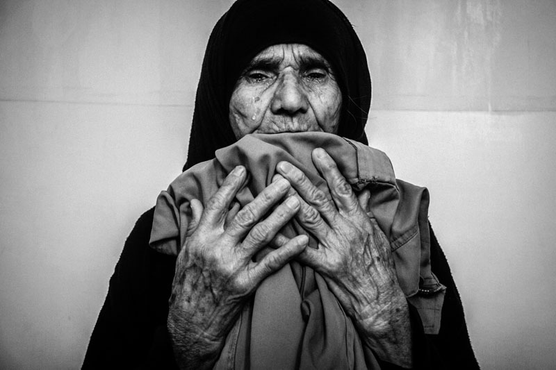 """During the Iran and Iraq war (1980-1988) more than 220, 000 Iranian soldiers were killed. After the war it was revealed that the bodies of over 10,000 Iranian soldiers were missing and there is still no sign of them. The mothers of Iranian soldiers, whose bodies were never returned, are crying for their lost sons every day. They do not know anything about their lost sons' bodies. Years of crying has damaged the eyesight of many of the mothers. Illam City, July, 25, 2013 Anbar Jaberi (72), who has waited 28 years for her son, is crying over her son's clothes. This is the only way for her to be calm. from my long-term project """"Mothers of patience""""."""