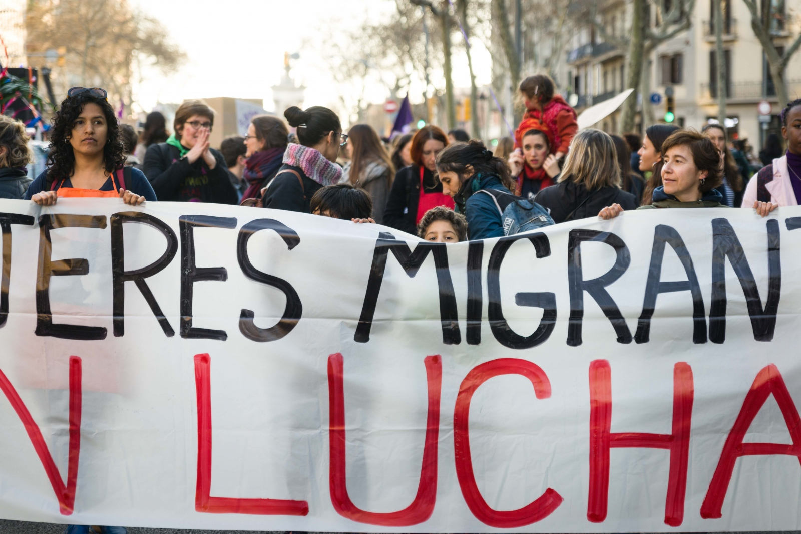 A child peaks over the banner of migrant women protesting on Internaional Women's Day 2019. Around 200.000 people filled Barcelona's Gran Via on the evening of March 8. The day was also a strike day for female workers in Spain: nationwide, around 6 million women participated in the strike. Barcelona, March 8, 2019.