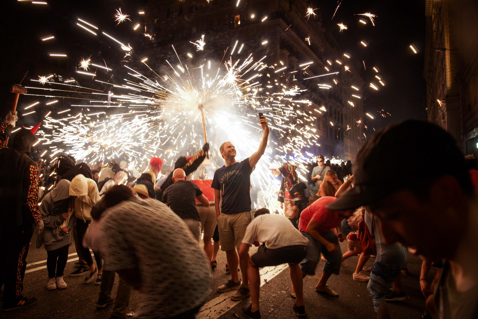 """A tourist defies the sparks at Catalonia's iconic """"fire-running"""" Correfoc at """"La Mercè"""". Barcelona, September 21, 2018."""