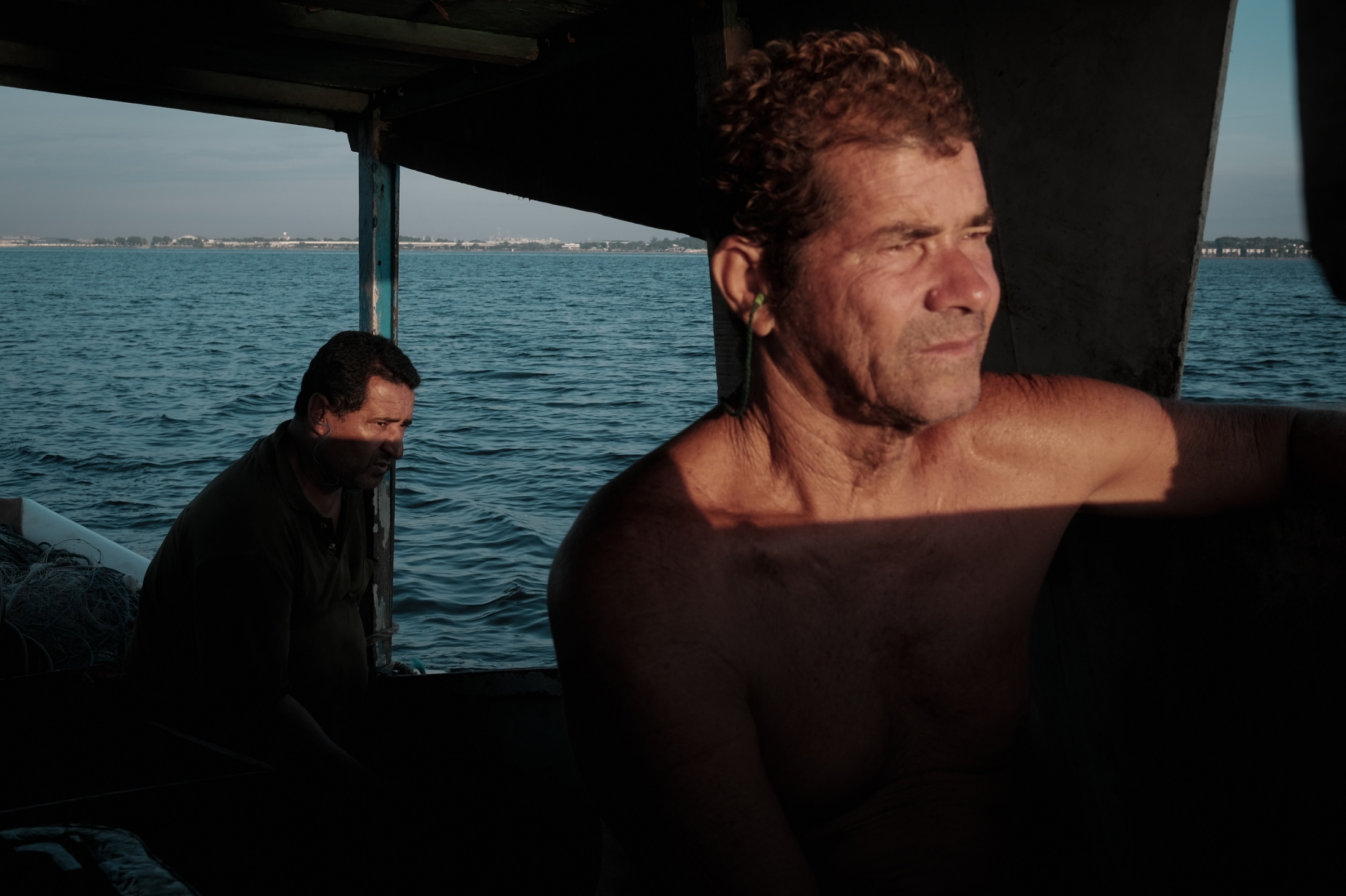 David (l) and Josué (r), two artesanal fishermen from Z-11 head out at dawn to try their luck. Artensanal fishermen use nets and ancient methods to fish in the once-bountiful bay, but their livelhoods have been under increasing strain for decades.