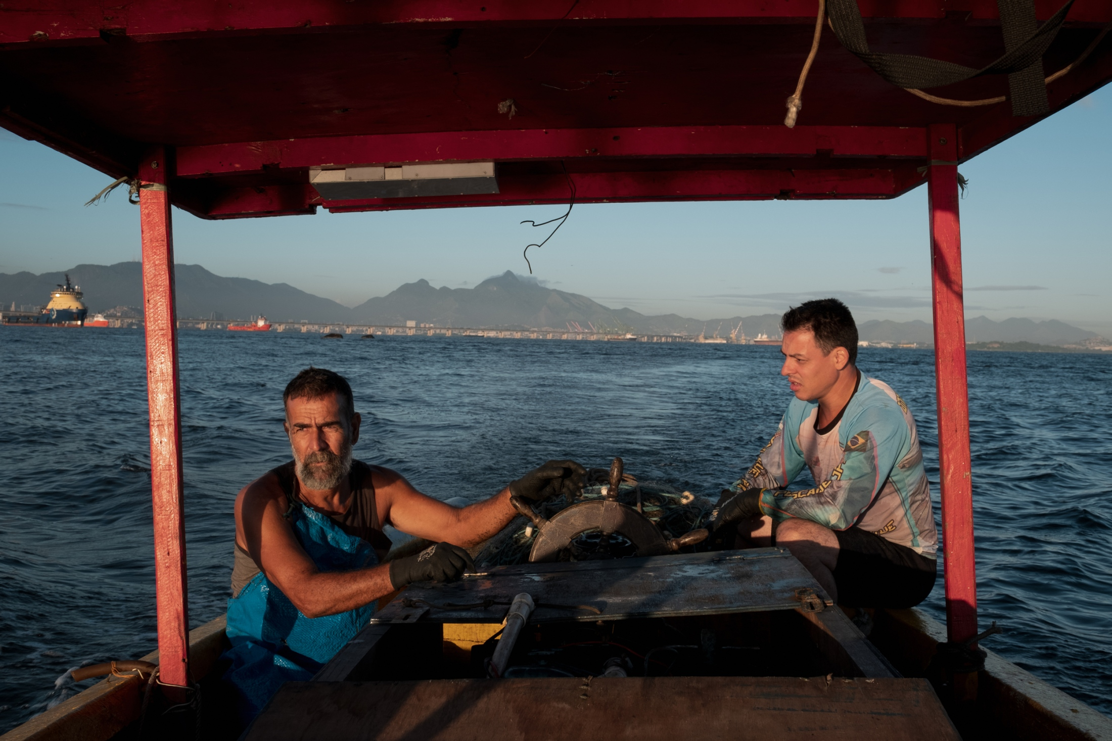 Fabio lives in the nearby favela of Roquette and has been fishing with Ataíde, who taught him. He works in a chemical plant on the other side of the bay, but still occasionally helps out Ataíde for some fish to bring home to his family. Ataide needs the help as hauling the nets by himself has become too difficult.