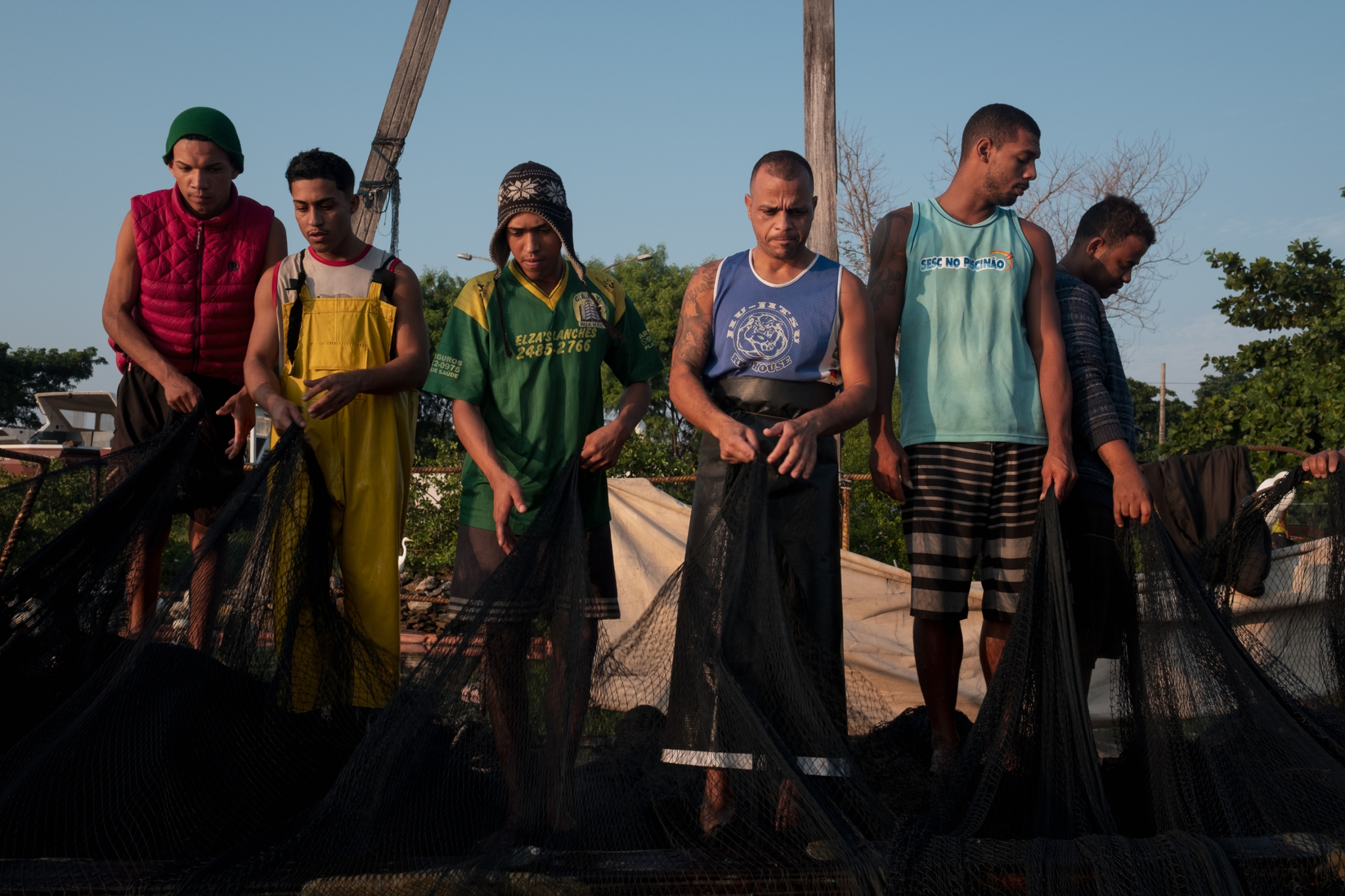 Fishermen haul the nets off of the boat to be ready for repairs and the next night of fishing.