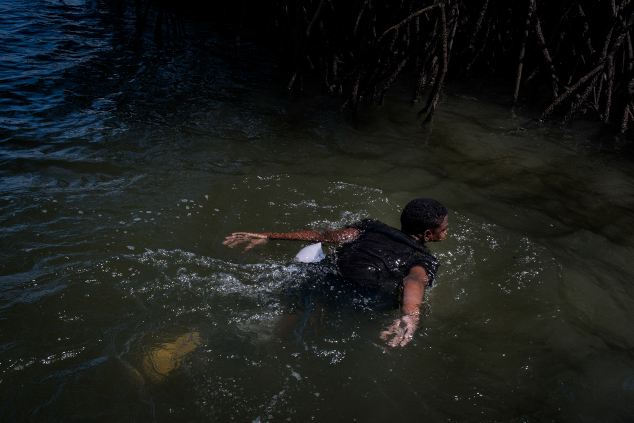 "A child ""conchero"" (a person who collects edible oysters) bathes in the river after his work in the mangrove. San Lorenzo, 2018. Johis Alarcón"