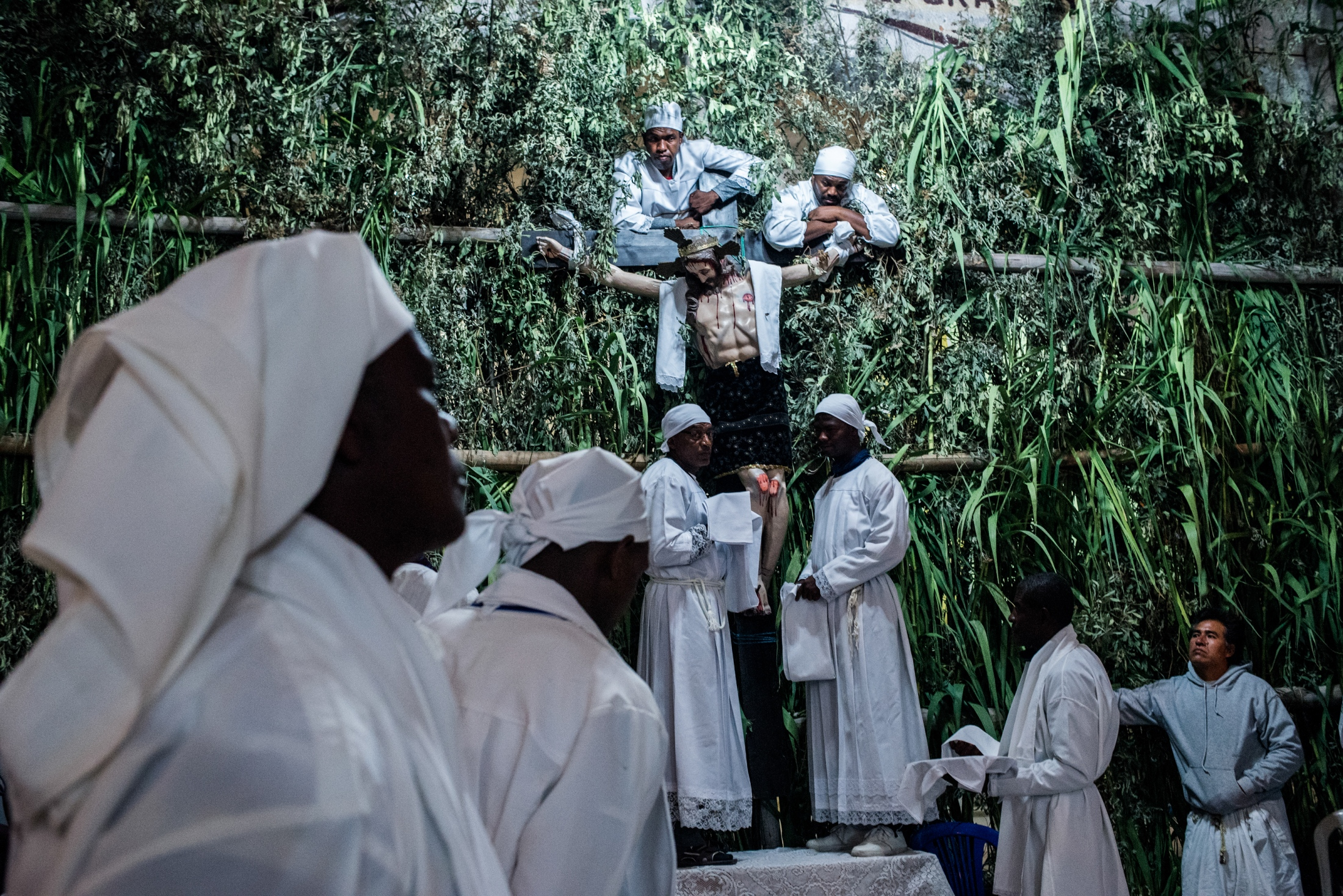Holy Week, the ritual celebrating the descent of Chris, takes place every year in the church of El Juncal. The men in white are in charge of carrying Christ down from the main altar and taking him to the procession. The statue is carried around the town streets among songs, candles and prayers. Juncal, 2018