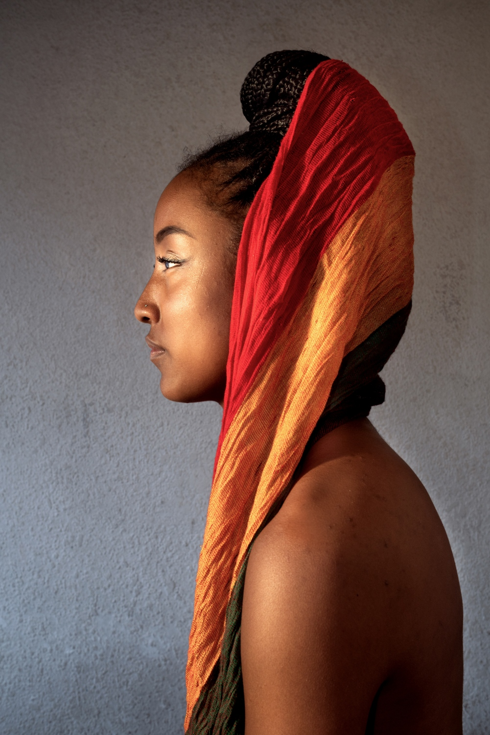 Katherine Ramos, 23, a member of the pan-African activist group Addis Ababa, keeps alive the traditions her grandmothers taught her on the use of turbans. She wears hers as a loose crown. Quito, Ecuador, 2019.  Johis Alarcón