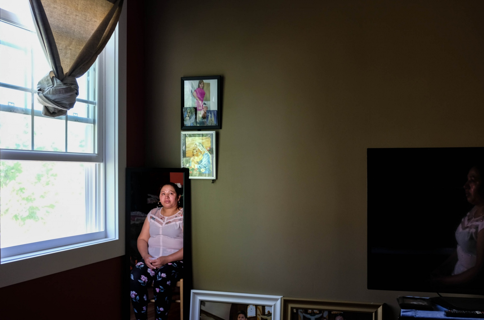 "Andrea Punin, 37, sister of the missing Jacqueline Punin, looking at a photograph on her bedroom wall. She says she wants to make an altar to honor her sister. Shot for "" Families of Missing Migrants Find Few Answers, Only Anguish.""  Gabriella N. Báez/NYT Institute"
