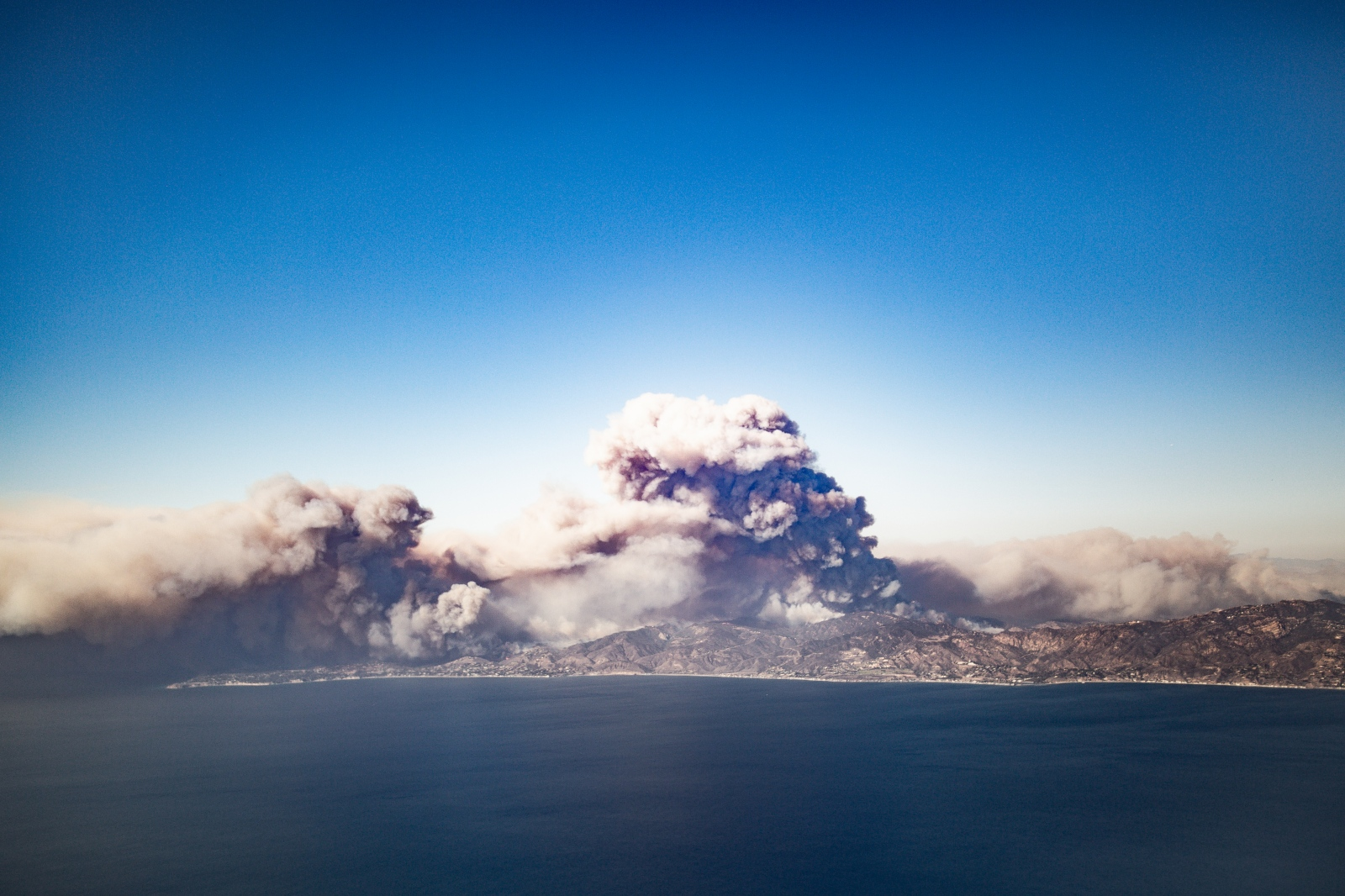 Photography image -  The Day of the Woolsey Fire - Nov. 8, 2018   This shot was taken right above the Woolsey Fire on the first day the fire broke out. Smoke plumes from the Santa Monica Mountain Range. We had quite a bit of distance between us and the fires but you could still feel the heat from the plane. Roughly 1600 structures were destroyed and just under 100,00 acres of land scorched. Fire season has become a year long event for California and despite the copious amount of rain that 2019 has received we must be ever vigilant to help prevent wildfire outbreaks.