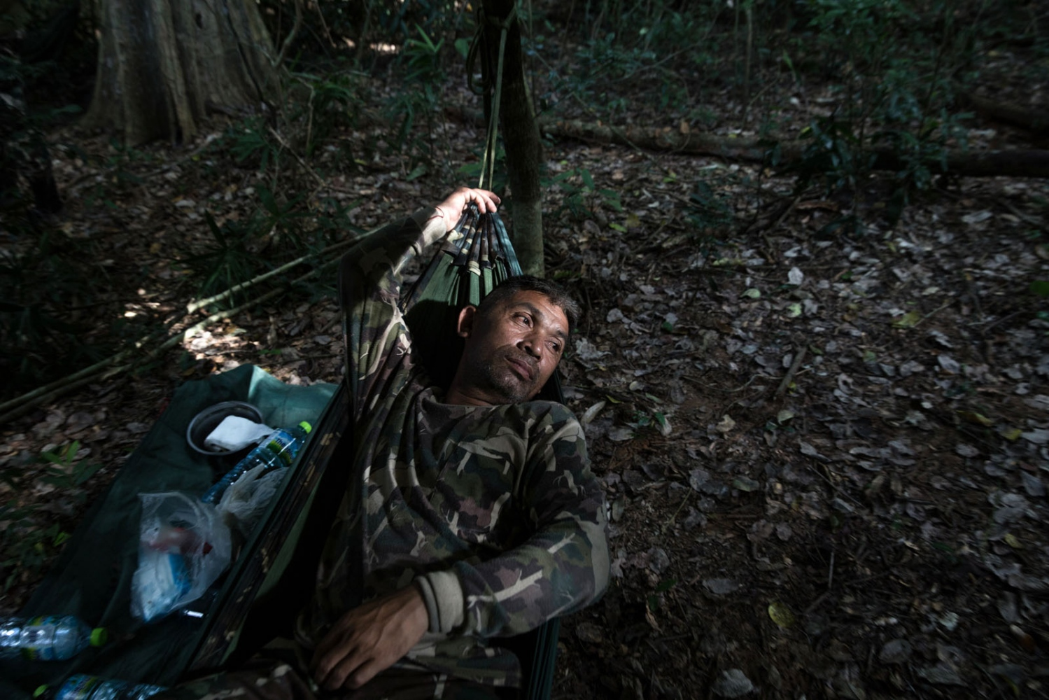 Ex-poacher Uten Pranpan, 46, made the decision to give up his old ways and instead protect the forest. Here he rests in a hammock during a 3-day patrol as part of a new recruit training course in eastern Thailand. Ta Praya National Park, Sa Kaew Province - September 2018