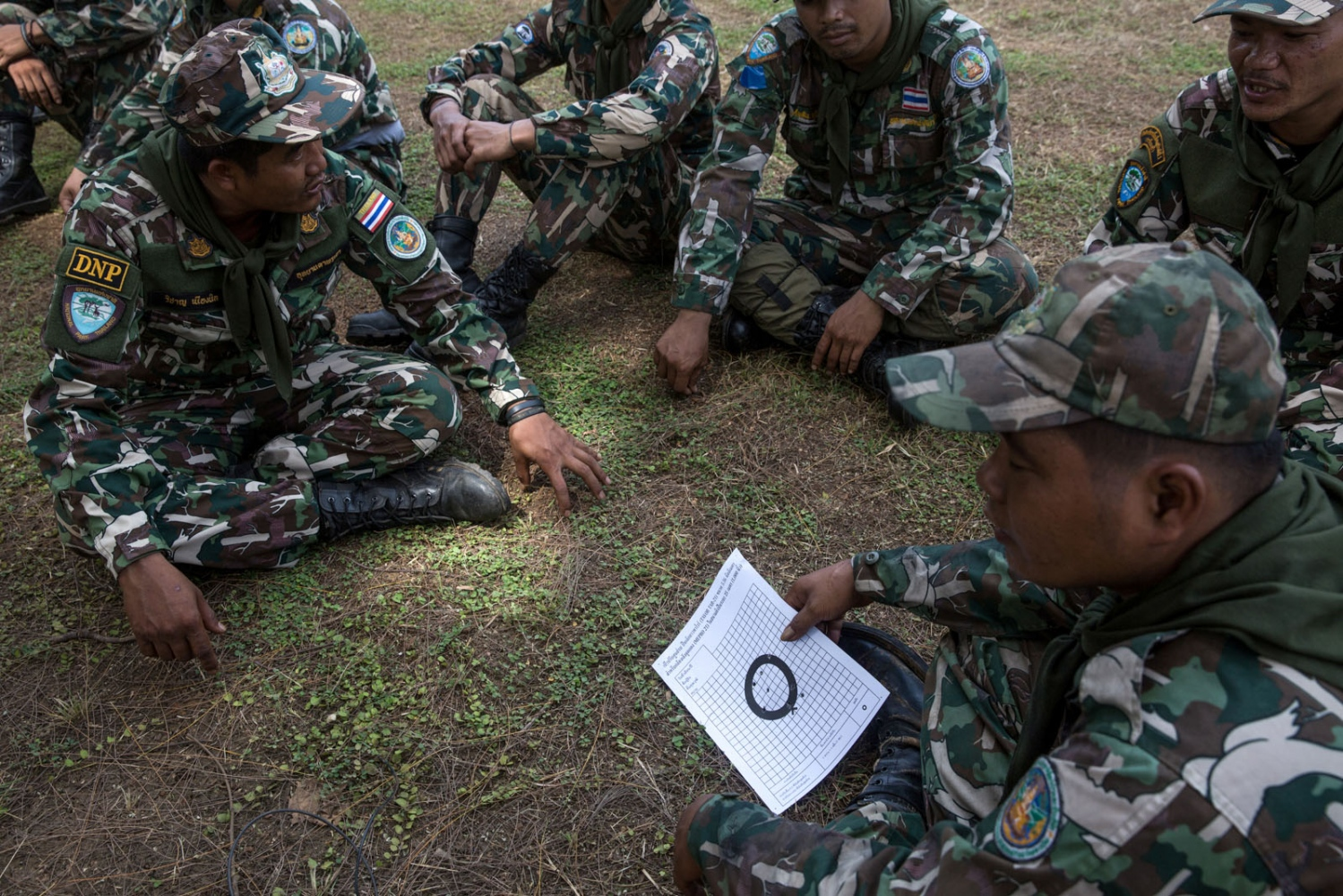 Thai forest rangers share each others target sheet after a weapons training session at a shooting range in a near by army base. Ta Praya National Park, Sa Kaew Province - September 2018
