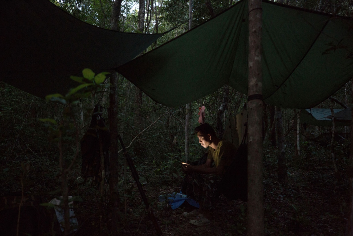 Sompob Khamprakon, 37, rests at camp looking at photos on his cell phone on the second night of a patrol in Ta Praya National Park in Eastern Thailand. This area is very close to the Cambodian border and sees a lot of poachers and illegal loggers operating within its boundaries. Ta Praya National Park, Sa Kaew Province - September 2018